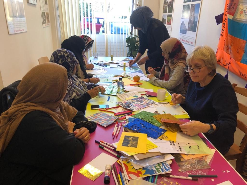 women at table in the cafe with materials during zinemaking workshop